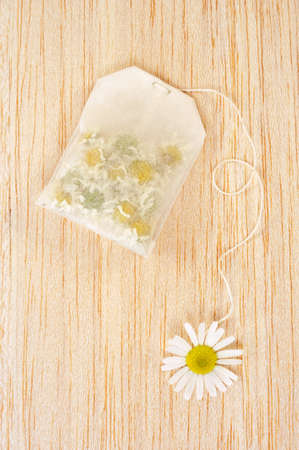 Bag of chamomile tea over wooden background - concept photo