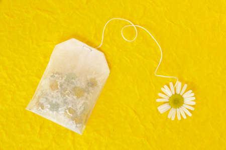 Bag of chamomile tea over yellow handmade paper - concept photo