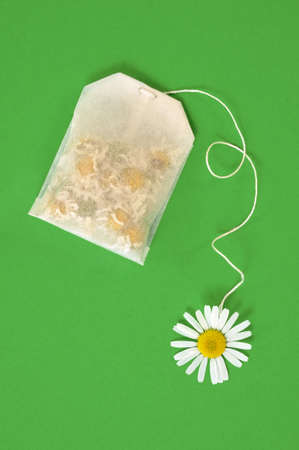 Bag of chamomile tea over green background - concept photo