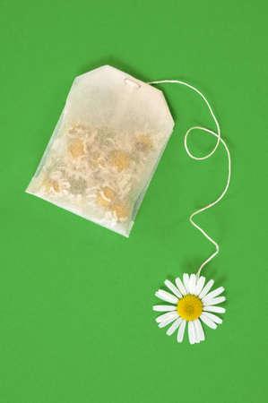 crisantemos: Bolsa de t� de manzanilla sobre fondo verde - concepto Foto de archivo