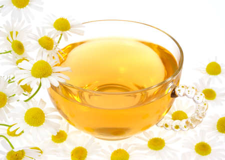 Cup of chamomile tea over white background photo