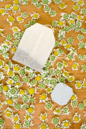 dried flower arrangement: Bag of chamomile tea with dry chamomilla flowers over wooden background