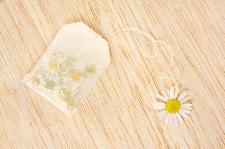 chamomile tea: Bag of chamomile tea over wooden background - concept Stock Photo