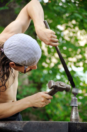 Young blacksmith hammering hot iron on anvil Stock Photo - 11274796
