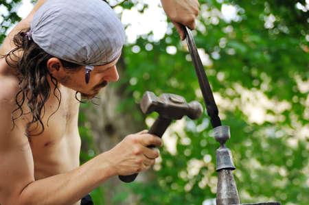 hammering: Young blacksmith hammering hot iron on anvil