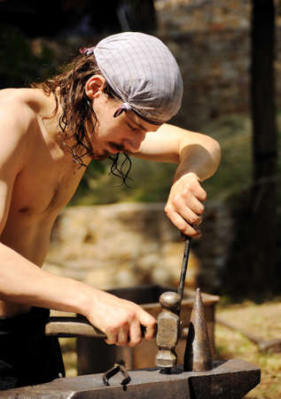 Young blacksmith hammering hot iron on anvil Stock Photo - 11274798