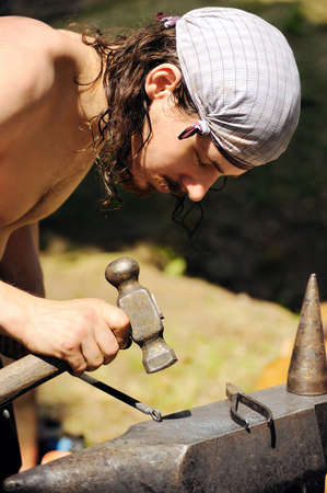 farriery: Young blacksmith hammering hot iron on anvil