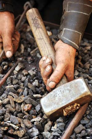 manos sucias: Detalle de las manos sucias sosteniendo un martillo - herrero