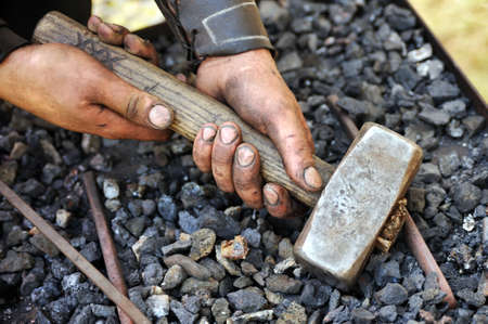 Detail of dirty hands holding hammer - blacksmith