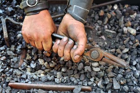manos sucias: Detalle de las manos sucias sosteniendo unos alicates - herrero