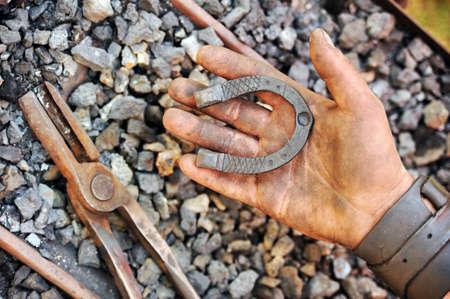 Detail of dirty hand holding horseshoe - blacksmith photo