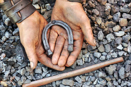 farriery: Detail of dirty hands holding horseshoe - blacksmith Stock Photo