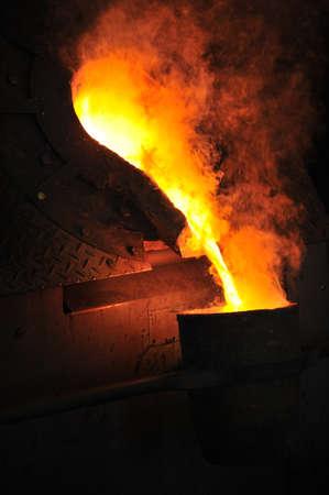 crisol: Fundici�n - metal fundido se vierte en la cuchara para la fundici�n Foto de archivo