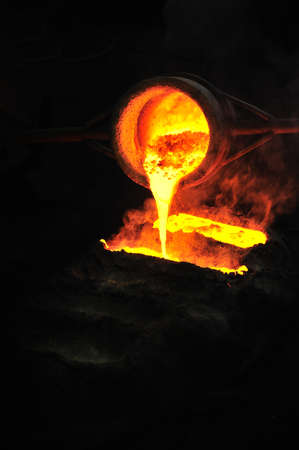 Foundry - molten metal poured from ladle into mould - emptying leftover Stock Photo