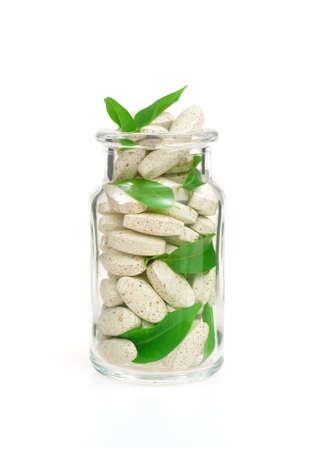 pill bottle prescription bottle: Herbal supplement pills and fresh leaves  in glass – alternative medicine concept