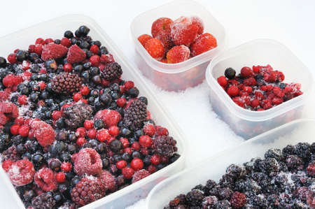 Plastic containers of frozen mixed berries in snow - red currant, cranberry, raspberry, blackberry, bilberry, blueberry, black currant, strawberry