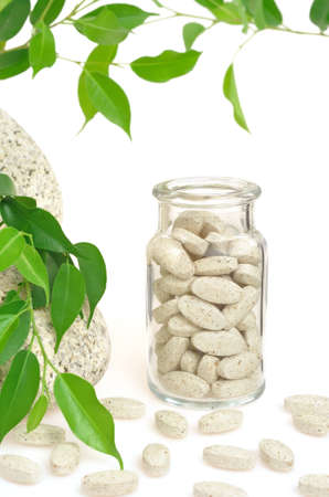 vitamins pills: Herbal supplement pills and fresh leaves  – alternative medicine still life Stock Photo