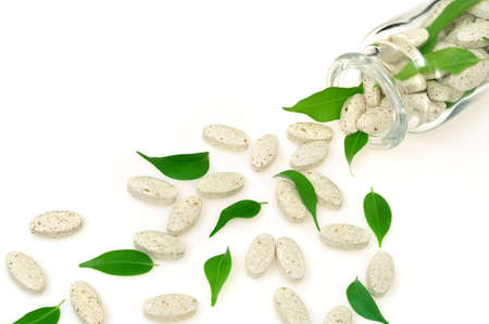 Herbal supplement pills and fresh leaves spilling out of bottle – alternative medicine concept