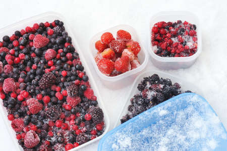 berry fruit: Plastic containers of frozen mixed berries in snow - red currant, cranberry, raspberry, blackberry, bilberry, blueberry, black currant, strawberry