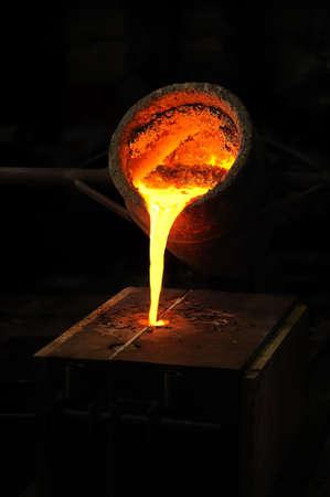 crisol: Fundici�n - metal fundido se vierte en el molde de la cuchara - fundici�n de cera perdida Foto de archivo