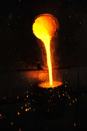 Foundry - molten metal poured from ladle for casting photo