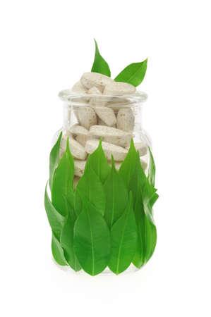 inmunidad: Pastillas de suplementos de hierbas y hojas frescas en concepto de medicina alternativa de vidrio