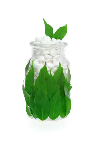 Herbal supplement pills and fresh leaves in glass – alternative medicine concept photo