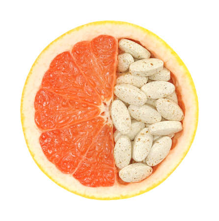 Close up of red grapefruit and pills isolated - vitamin concept photo