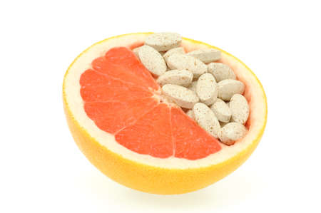 Close up of red grapefruit and pills isolated - vitamin concept Stock Photo