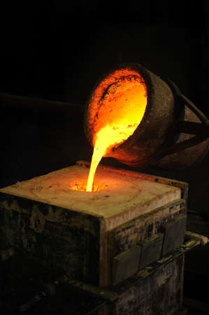 Foundry - molten metal poured from ladle into mould - lost wax casting photo