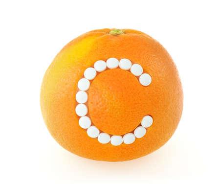 inmunidad: Pomelo con píldoras de vitamina C a lo largo de fondo blanco para el concepto de