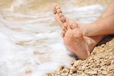 Relaxation on beach, detail of male feet Standard-Bild