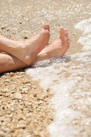 Relaxation on beach, detail of male feet photo