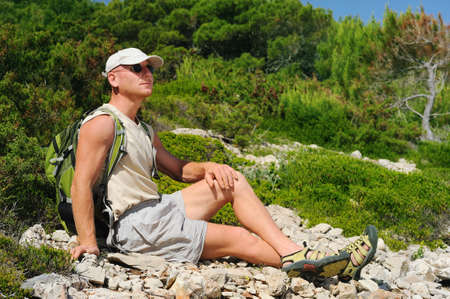 30 40: Outdoor man resting on rock after hiking, Croatia