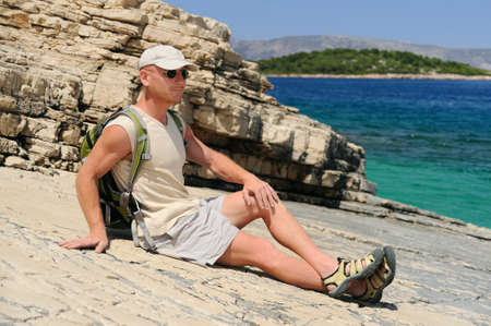 Outdoor man resting on rock after hiking, Croatia photo