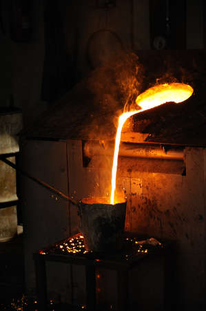 ferrous foundry: Foundry - Molten metal poured from lathe for casting