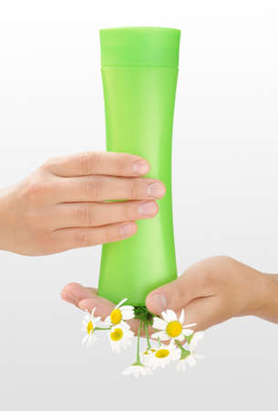 Hands of young woman holding cosmetics bottle and fresh chamomile photo