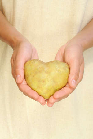 Hands of young woman holding potato in heart shape photo