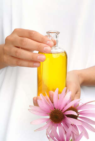 botanical remedy: Hands of young woman holding essential oil and fresh coneflowers Stock Photo