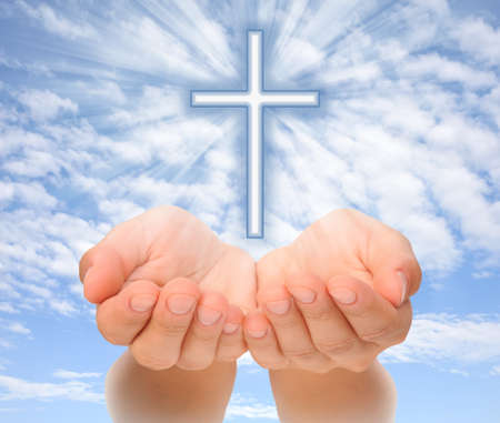 Hands holding Christian cross with light beams over sky photo