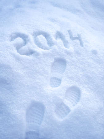 Foot step prints in snow, New Year 2014 concept photo