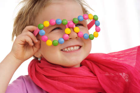concept and ideas: Portrait of cute little girl wearing funny glasses, decorated with colorful sweets, smarties, candies