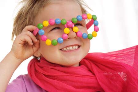 Portret van schattig meisje draagt grappige bril, versierd met kleurrijke snoepjes, wijsneuzen, snoepjes