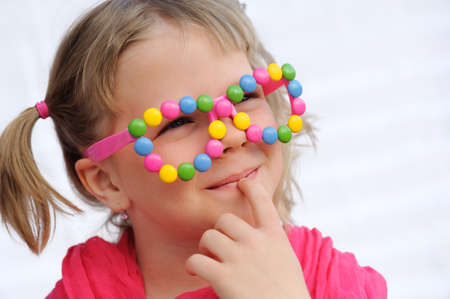 6 7 year old: Portrait of cute little girl wearing funny glasses, decorated with colorful sweets, smarties, candies