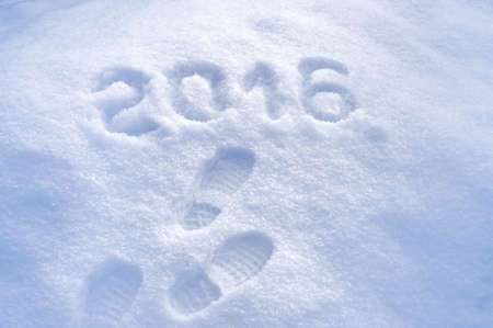 snow ground: Foot step prints in snow, New Year 2016 greeting