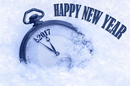 pocket watch: 2017 Happy New Year, New Year 2017 greeting card, pocket watch in snow, English text