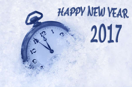 new beginning: New Year 2017 greeting in English language, pocket watch in snow, happy new year 2017 text Stock Photo
