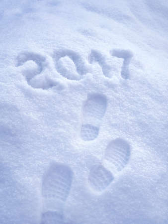 foot step: 2017 New Year greeting card, 2017 new year, foot step prints in snow, happy new year 2017 concept Stock Photo