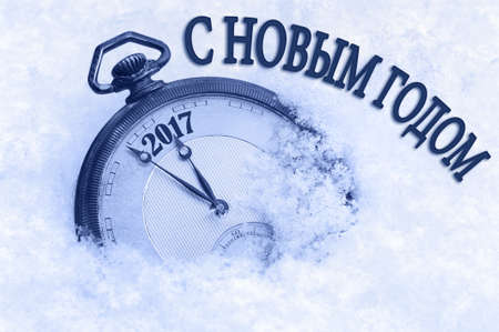 snow field: 2017 new year, Happy New Year greeting in Russian language, pocket watch in snow