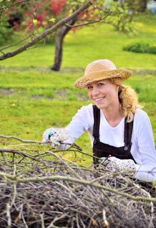 Young woman working in orchard, after tree pruning, pile of cut branches and twigs of fruit trees, cutting branches of apple trees in garden, smiling woman piling up brushwood in spring photo